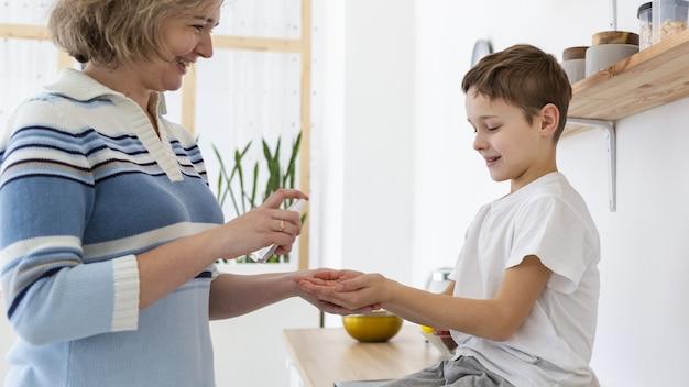 Vue côté, de, mère, donner, fils, désinfectant pour les mains