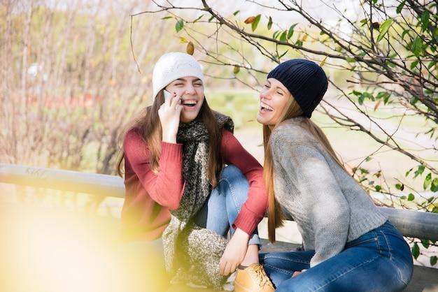 Vue de côté, moyen, deux jeunes femmes discutant dans le parc
