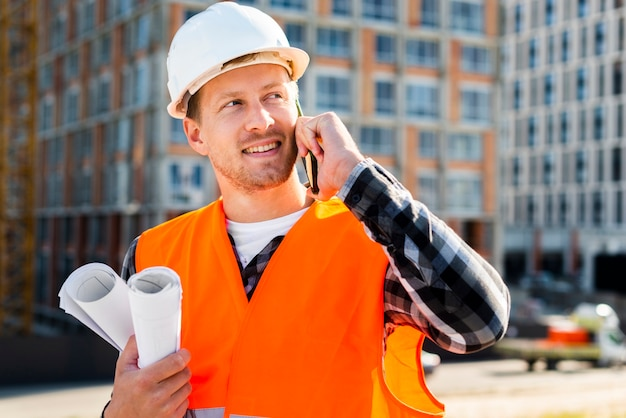 Vue de côté moyen d'ingénieur parlant au téléphone