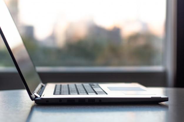Vue côté, de, ordinateur portable bureau, sur, table bureau, à, fond ville