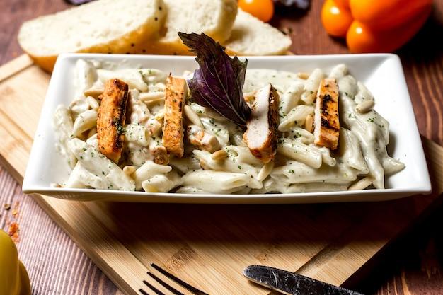 Vue de côté des pâtes au fromage et au poulet avec des tranches de pain