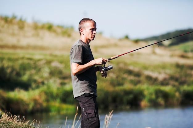 Vue côté, de, a, pêcheur, tenue, canne à pêche
