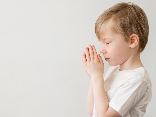 Vue côté, de, petit garçon, prier