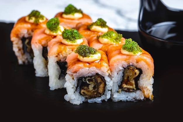 Vue de côté philadelphia roll avec sauce au saumon poisson frit et caviar tobiko sur le dessus