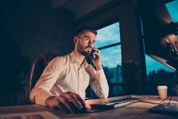Vue de côté de profil de travailleur concentré s'asseoir à table de travail de bureau sur son smartphone