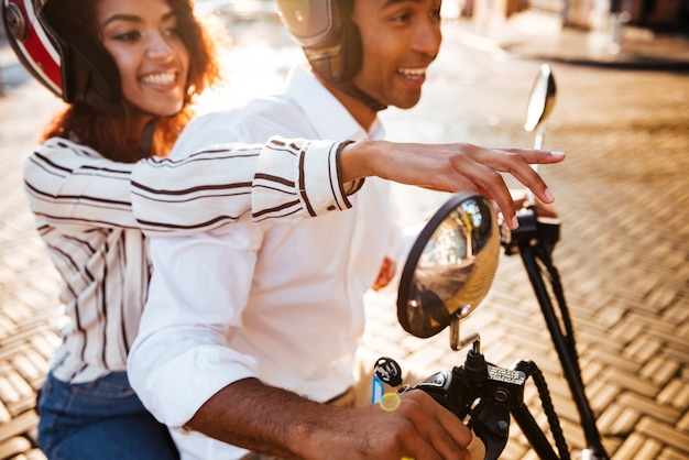 Vue de côté recadrée de couple africain heureux monte sur une moto moderne dans la rue