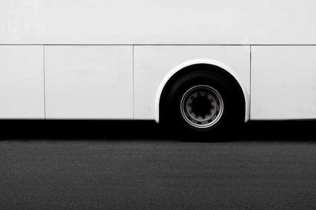 Vue de côté d'une roue de bus blanche sur une route goudronnée.