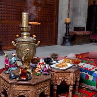 Vue de côté samovar avec verre de thé et figurines et baklava en table sur restaurant