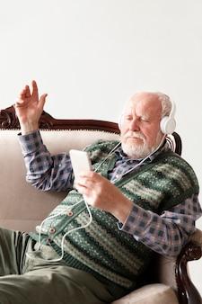 Vue de côté senior sur un canapé en jouant de la musique
