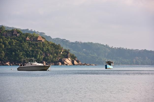 Vue sur la côte des seychelles avec un bateaux sur un premier plan