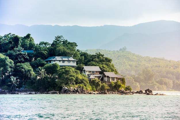 Vue sur la côte des seychelles avec des maisons dans la forêt