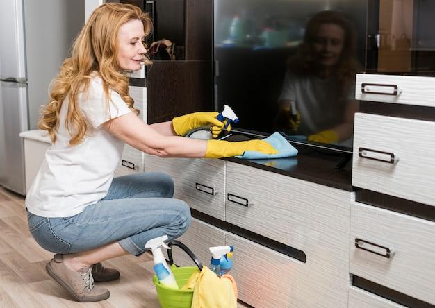 Vue côté, de, smiley, femme, nettoyage, meubles