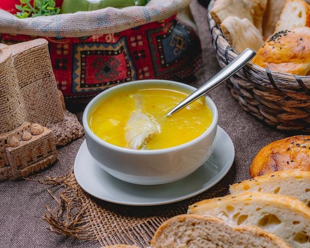 Vue de côté soupe au poulet dans un bol avec cuisse de poulet et braed sur la table