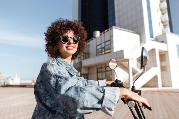 Vue côté, de, sourire, bouclé, femme, dans, lunettes soleil, poser, sur, moderne, moto, dehors, et, regarder loin