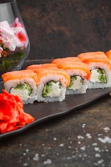 Vue de côté sushi serti de gingembre mariné en plaque sombre