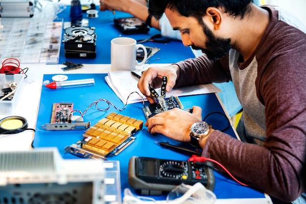 Vue de côté des techniciens travaillant sur des pièces électroniques