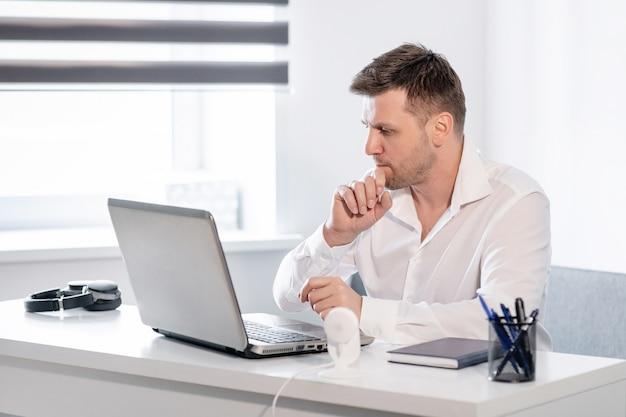Vue de côté tourné de songeur jeune homme assis à la maison et travaillant sur ordinateur portable. homme de race blanche travaillant à domicile.