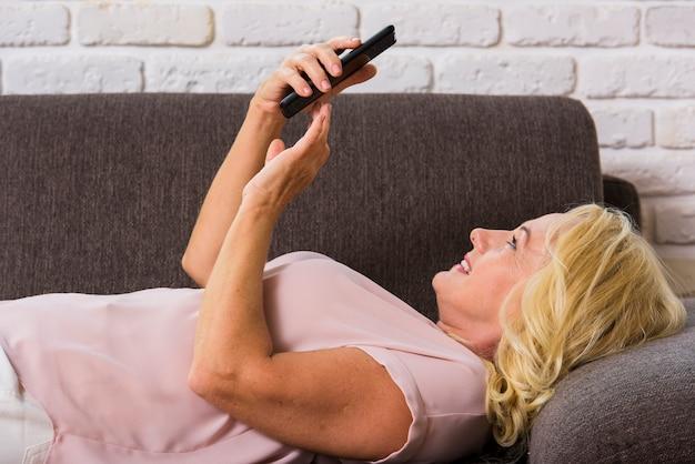 Vue de côté vieille dame regardant son téléphone