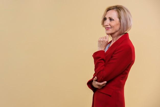 Vue de côté vieille femme vêtue d'une veste rouge