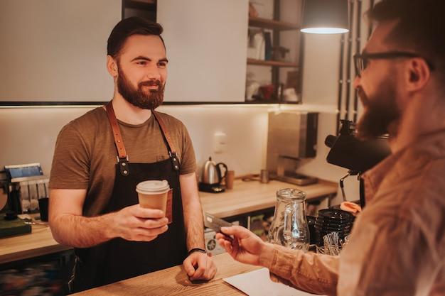 Vue en coupe d'un barman portant un tablier et debout derrière la table du bar et donnant une tasse de café au client. en même temps, le client donne au barman une carte de crédit pour payer le café.