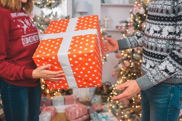 Vue en coupe de femme avec boîte rouge avec cadeau. il a un ruban blanc autour. l'homme va le prendre. il atteint pour présenter avec les mains.
