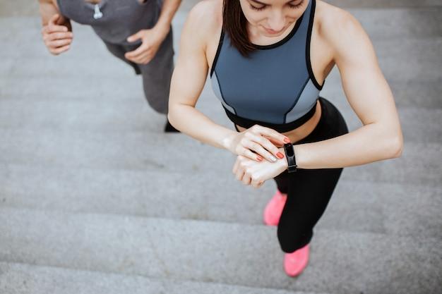 Vue en coupe d'une fille qui monte par étapes. elle regarde sa montre. il y a un gars qui va derrière elle. un couple bien construit fait du jogging.