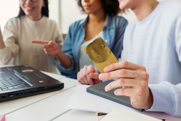 Vue en coupe d'un gars qui tient une carte de crédit dans ses mains pendant qu'il regarde un ordinateur portable avec des filles ensemble.