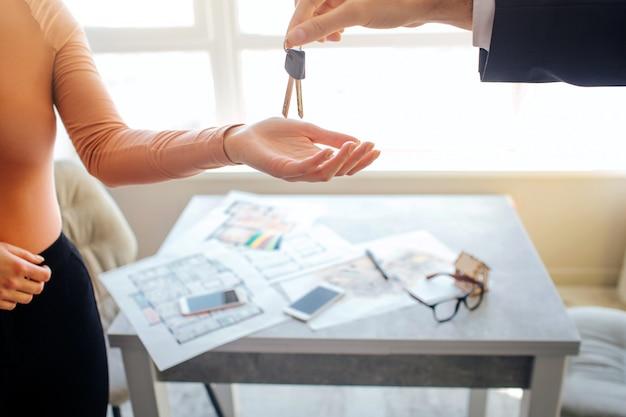Vue en coupe d'une jeune femme acheter ou louer un appartement. elle atteint la main et obtient les clés de l'agent immobilier.