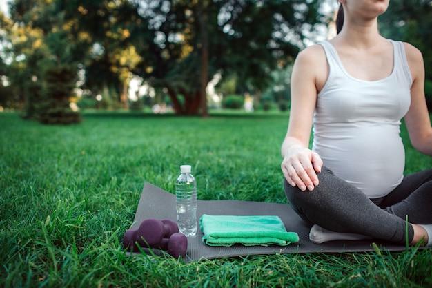 Vue coupée de la jeune femme enceinte s'asseoir en posture de lotus sur un compagnon de yoga dans la chambre. elle a une bouteille d'eau, des haltères et une serviette verte.