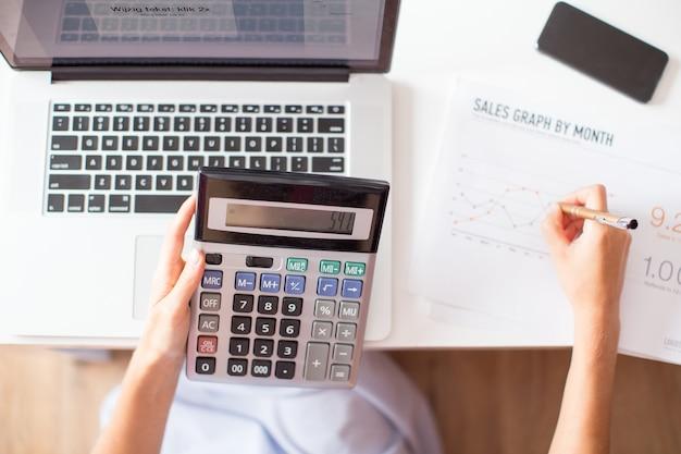 Vue croisée du gestionnaire des ventes utilisant la calculatrice