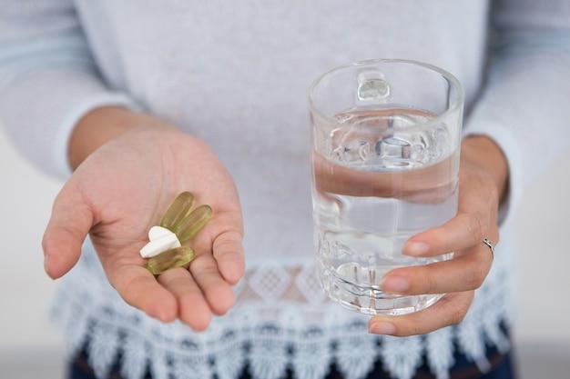 Vue croisée de la fille avec des pilules et un verre d'eau