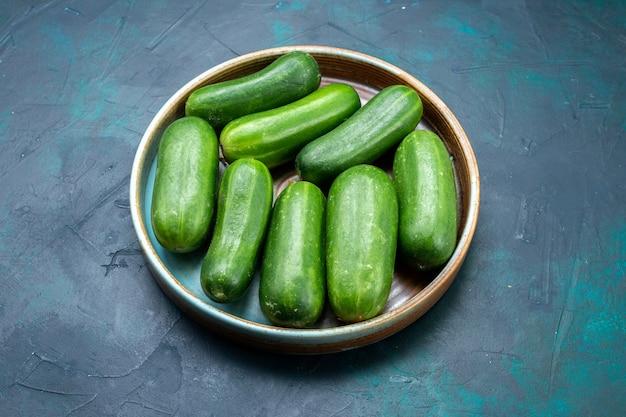 Vue demi-dessus concombres verts frais légumes mûrs à l'intérieur de la plaque sur un bureau bleu foncé.