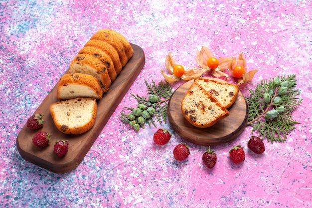 Vue demi-dessus délicieux gâteau sucré et délicieux tranché avec des fraises rouges fraîches sur plancher rose.