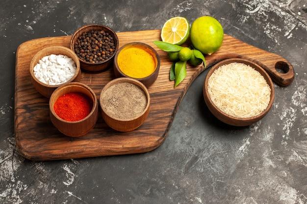 Vue demi-dessus du riz cru avec des citrons et des assaisonnements sur des épices alimentaires crues de surface sombre