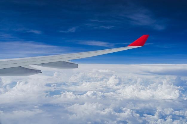 Vue depuis la fenêtre de l'avion et l'aile avec des nuages duveteux, volant et voyageant
