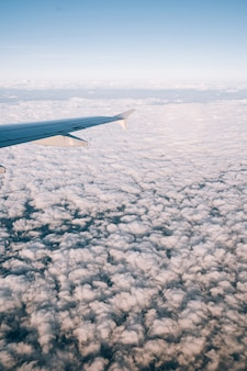 Vue depuis la fenêtre de l'avion sur les cumulus blancs ci-dessous