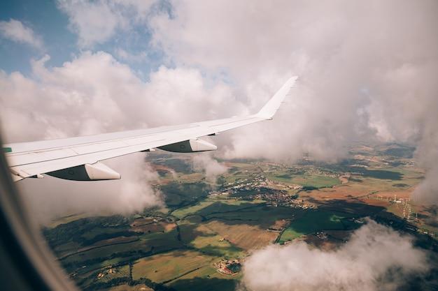 Vue depuis la fenêtre de l'avion vers le sol ci-dessous à travers les nuages