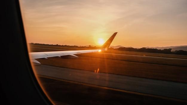 Vue depuis la fenêtre de l'avion voir les ailes d'un avion avec un coucher de soleil à l'heure d'or.