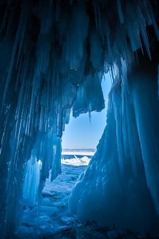 Vue depuis une grotte de glace avec d'énormes glaçons bleus sur les stalactites de cristal du lac baïkal au plafond