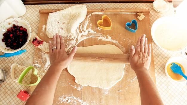 Vue depuis le haut sur une jeune femme faisant de la pâte et la roulant avec un rouleau à pâtisserie en bois sur un comptoir de cuisine