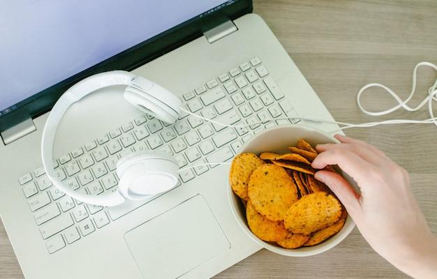 Vue depuis le haut de l'ordinateur portable, des écouteurs et des mains féminines avec des puces
