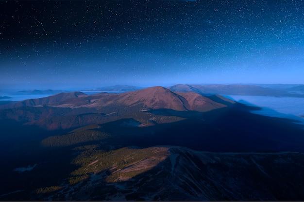 Vue depuis hoverla, sur le ciel étoilé au-dessus des sommets des carpates.