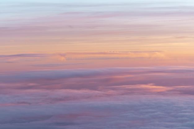 La vue depuis le hublot de l'avion sur le ciel est de couleur orange-rose avec des nuages aériens