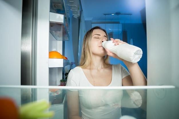 Vue depuis l'intérieur du réfrigérateur sur une jeune femme buvant du lait la nuit