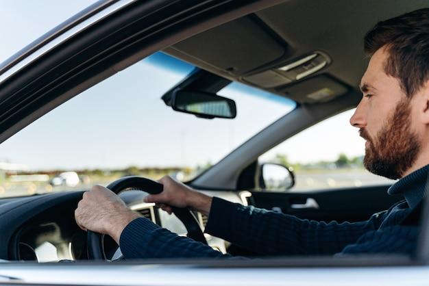 Vue depuis la rue du bel homme d'affaires conduisant une voiture avant d'acheter. un homme élégant et séduisant en affaires ferme la voiture au volant. notion de transport