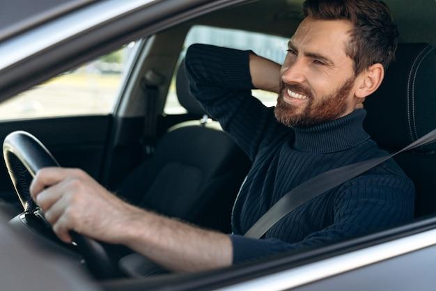 Vue depuis la rue du jeune homme se frottant le cou douloureux, tout en ayant l'air fatigué de conduire. conducteur masculin ayant des douleurs au cou, assis dans sa voiture