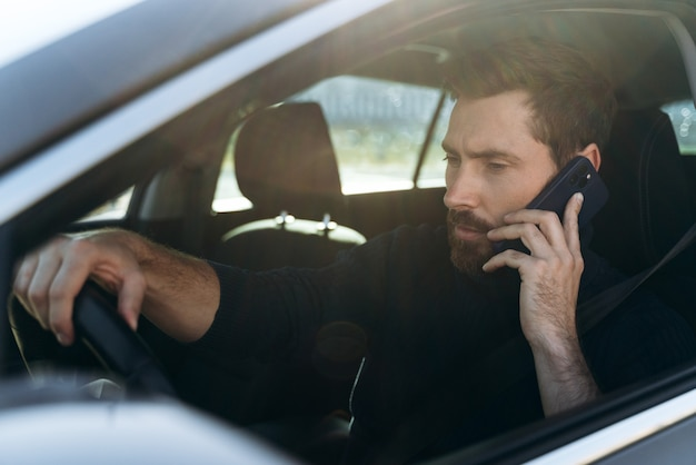 Vue depuis la rue sur l'homme caucasien concentré regardant la fenêtre tout en discutant via smartphone avec son collègue pendant le long trajet jusqu'au travail