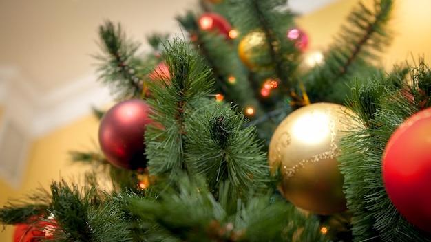 Vue depuis le sol sur un magnifique sapin de noël décoré avec des lumières rougeoyantes et des boules étincelantes. arrière-plan abstrait parfait pour les vacances d'hiver ou les célébrations