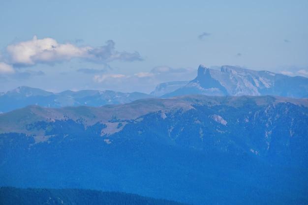 Vue depuis le sommet du mont jusqu'aux chaînes de montagnes lointaines à l'horizon dans une brume bleue