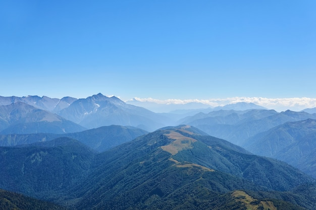 Vue depuis le sommet du mont oshten jusqu'aux chaînes lointaines des montagnes du caucase dans une brume bleue